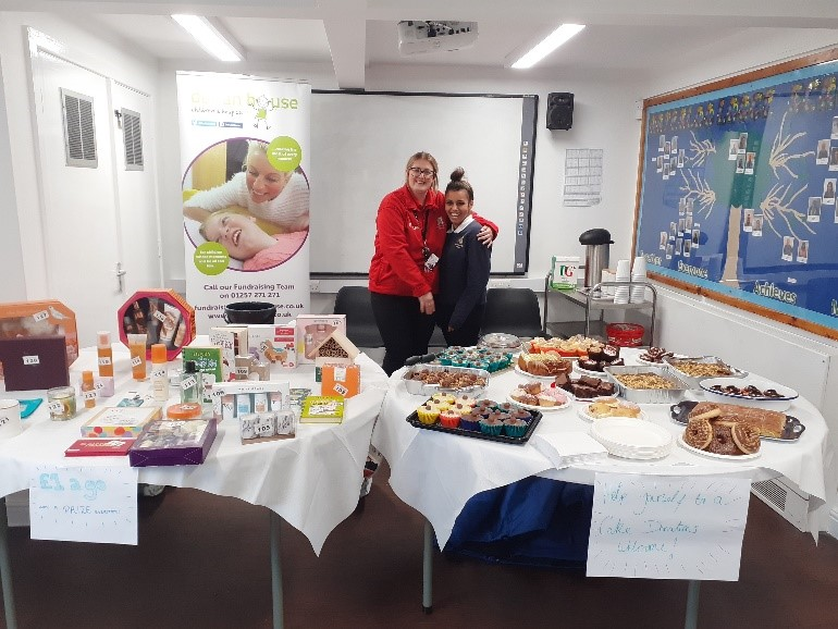 Staff and pupil pose for a photograph having set up the cake stall displays.